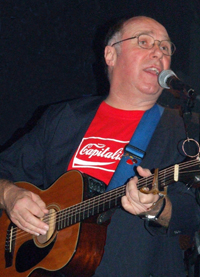 Shep Woolley on stage with guitar.